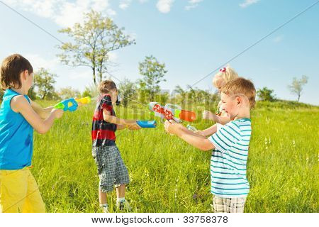 Kids group with water guns and soakers shooting