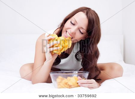 pretty woman eating potato chips in bed at home