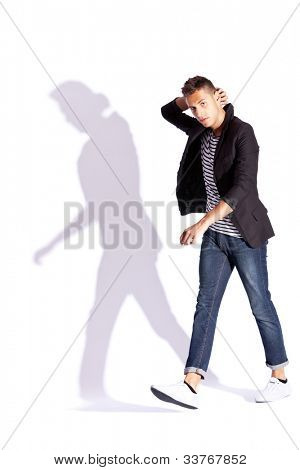 fashionable man walking and looking at the camera, while holding his hand on the back of his head, on white background with hard shadow