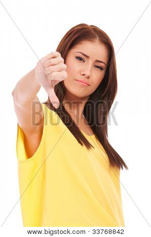 Portrait of beautiful young woman gesturing thumbs down on white background