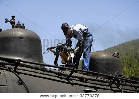 A Railway Man Inspecting Engine Bell