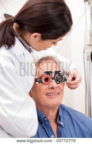 Optometrista hembra ajuste lente de ensayos marcos de hombre maduro