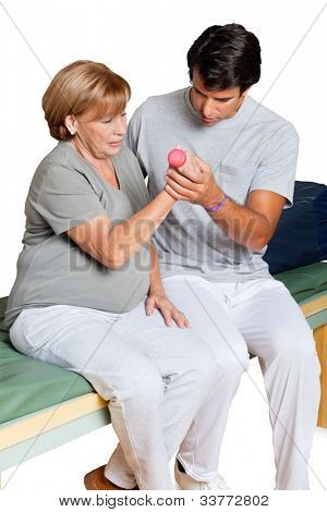 Young therapist giving muscle training for elbow joint over white background
