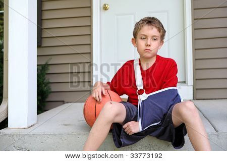 Boy with arm in a sling sitting with a basketball