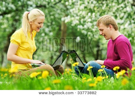 Group of two young students studying with computer in spring outdoors