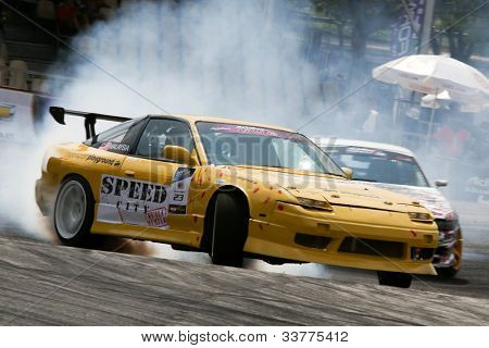 KUALA LUMPUR - MAY 20: Malaysia's Kevin Rajoo (car #23) leaves a trail of smoke as he drifts in this qualifying run during the Formula Drift 2012 Asia Round 1 on May 20, 2012 in Speedcity, Malaysia.