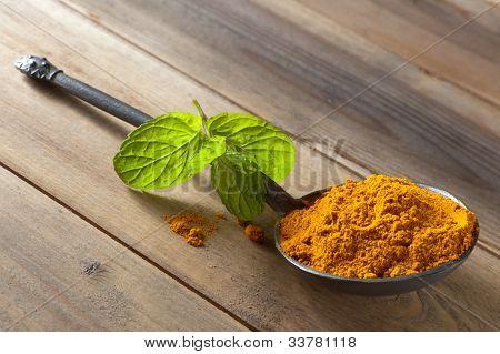 Yellow turmeric or curcuma spice in a pewter spoon