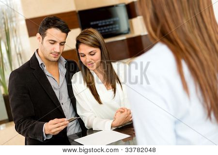 Couple doing the check-in at a hotel paying by credit card