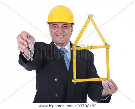 Senior architect yellow helmet holding wooden ruler folded in house shape and keys - over white background