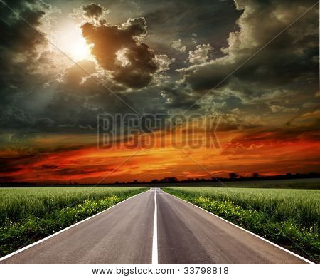 Asphalt road through the fields at sunset
