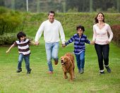 Happy family running outdoors chasing a dog