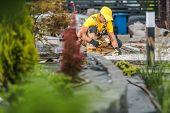 Garden Path Work. Caucasian Men In His 30s Building Granite Backyard Garden Path. poster
