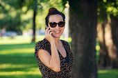 Woman Speaking On The Phone. Woman Speaking On The Cell Phone. Portrait Of Woman Speaking On The Cel poster