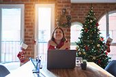 Beautiful woman sitting at the table working with laptop at home around christmas tree Hugging onese poster