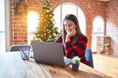 Beautiful woman sitting at the table working with laptop at home around christmas tree with a happy  poster