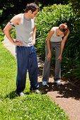 Man wearing a pedometer watching a woman as she is bent over while recovering next to bushes