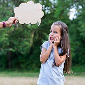 Pretty surprised thinking little girl posing summer nature outdoor with cloud of thoughts (like in c poster