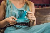 Young Woman Having A Mediterranean Breakfast Seated At Sofa And Drinks Hot Aromatic Coffee poster