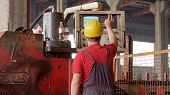 An Employee In Helmet Operating A Metal Processing Machine That Manufactures Sheet Metal For Further poster