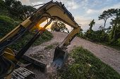 The Modern Excavator On The Construction Site With Sunset Sky. Large Tracked Excavator Standing On A poster