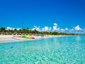 The beautiful beach of Varadero in Cuba with colorful boats and thatched umbrellas (image taken from