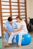 stock photo of physical therapist  - Young physical therapist examining senior woman - JPG