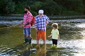 Man With His Son And Father On River Fishing With Fishing Rods. Boy With Father And Grandfather Fly  poster