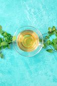 Mint Tea Cup, Overhead Shot On A Vibrant Turquoise Background With Fresh Mint Leaves And Copyspace poster