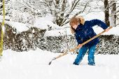 Child Shoveling Snow. Little Boy With Spade Clearing Driveway After Winter Snowstorm. Kids Clear Pat poster