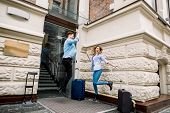 Young Cheerful Couple With Suitcases Jumping And Giving Five, Having Fun, Before Arriving To The Hot poster