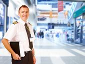 Airline captain pilot wearing uniform with epaulettes standing at airport with his flight documents.