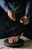 Mans Hands Sprinkled With Salt Raw Uncooked Black Angus Beef Tomahawk Steak On Bones On Linen Table  poster