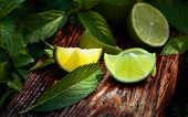 Wet Growing Mint In The Garden And Lime Slices. Lime Slices And Mint Leaves On An Old Wooden Backgro poster