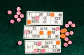 Lotto, Classic Family Board Game. Several Wooden Barrels, Orange Chips And Three Cards On Green Velv poster