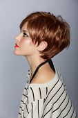 profile of a beautiful woman with red lips and short feathered red hair in modern bob over studio ba