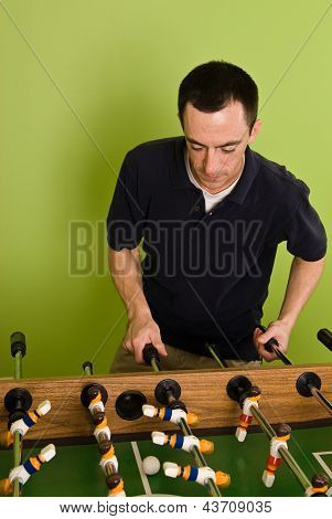 Caucasian male playing Foosball, table football