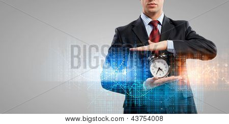 Business man holding alarmclock