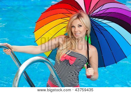 Beautiful Girl By The Pool With Colored Umbrella