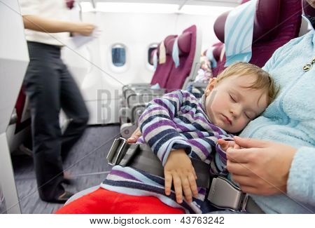 Mother And Sleeping Two Year Old Baby Girl Travel On Airplane