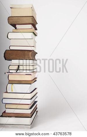 A Pile Of New And Old Books On A White Grey Background