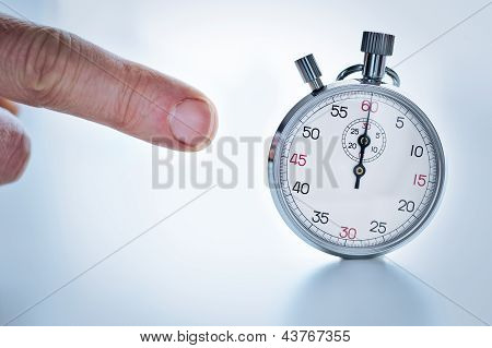Human finger pointing a stopwatch