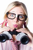 image of prissy  - Conceptual image of a nerdy brainy businesswoman making a moue of surprise as she looks through binoculars to study future development - JPG
