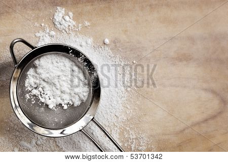 Icing or confectioner's sugar in sifter, over baking paper.