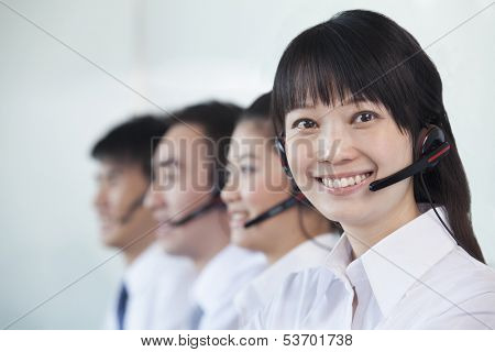 White collar workers in row with headsets