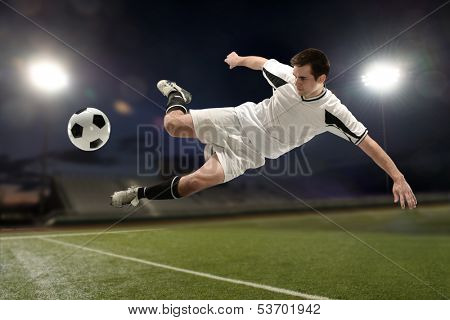 Soccer player jumping and kicking the ball inside a stadium at night
