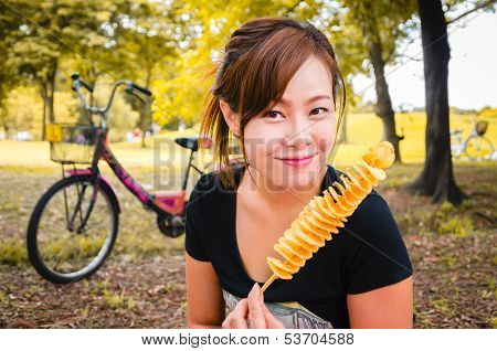 Beautiful happy asian woman enjoy her snack in park