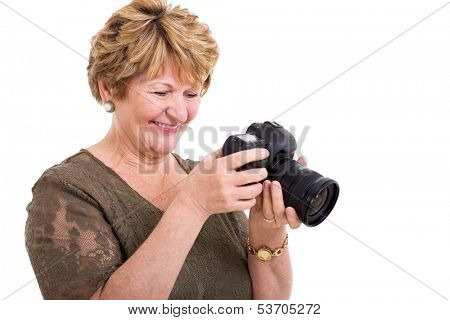 cheerful retired senior woman viewing photos on a digital SLR camera