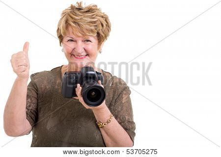 happy senior woman holding a modern SLR camera and giving thumb up