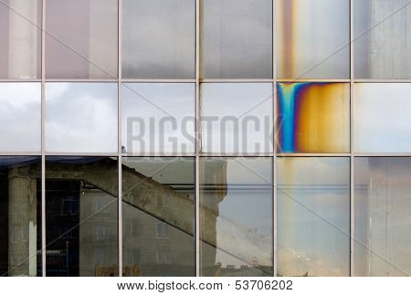 Abstract Industrial Background With Glassed Facade Of Modern Building And Oxide Tint On One Element