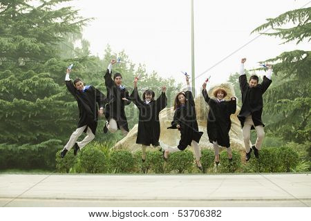Young group of graduates jumping